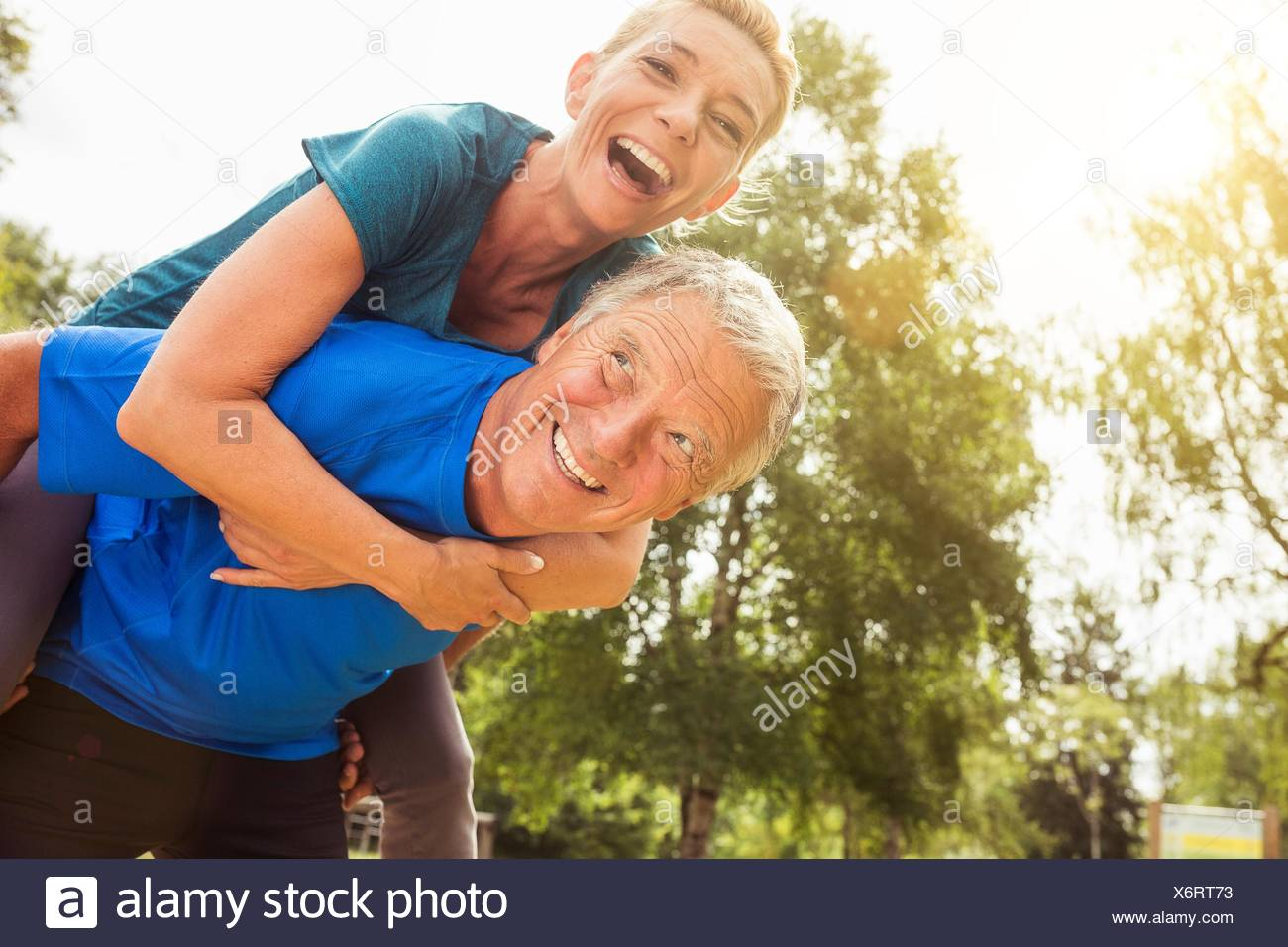 Senior man carrying mature woman on back, outdoors, laughing - Stock Image