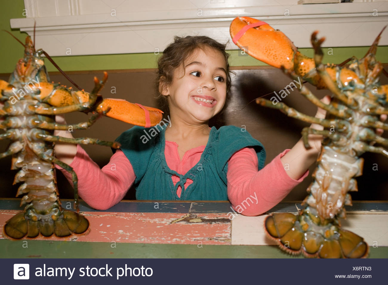 Young girl holding two live lobsters - Stock Image