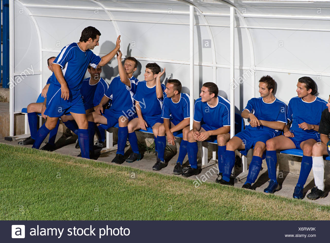 Footballer celebrating with team mates - Stock Image