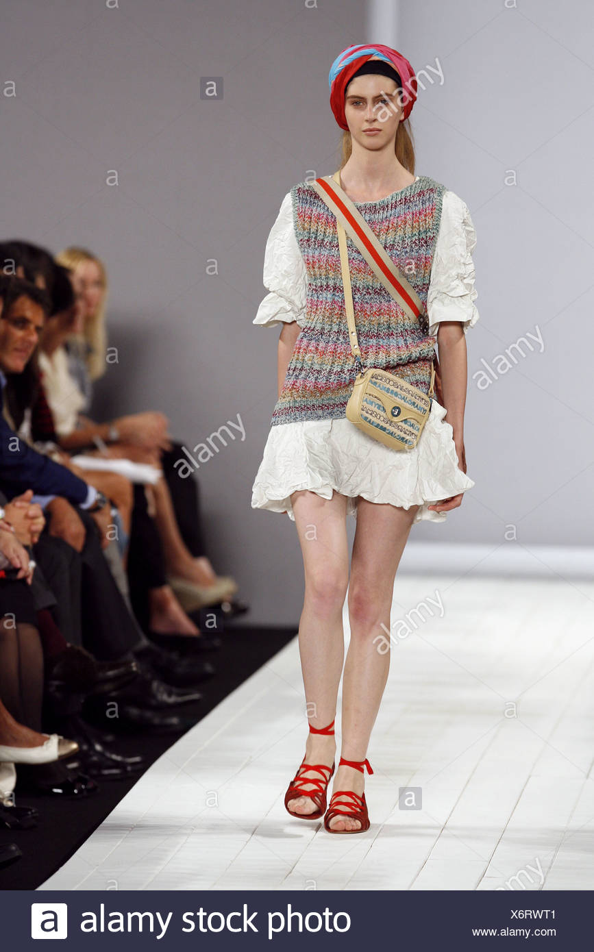 Model wearing a cream crinkled oversized minidress, oversized mulitcoloured knitted tank top, beige across the body purse, - Stock Image