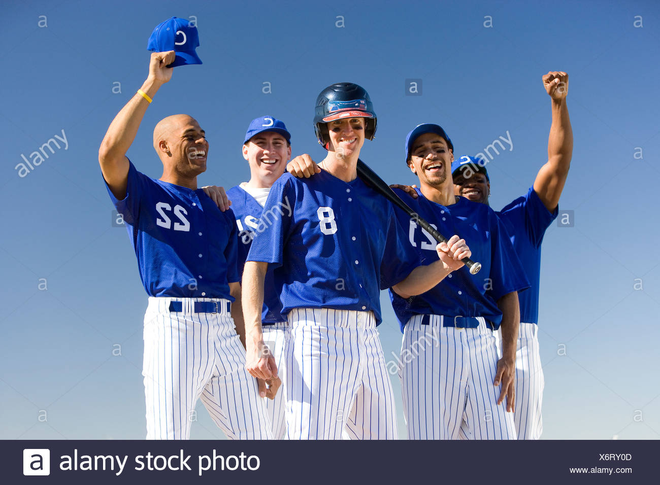 Baseball team, in blue uniforms, celebrating victory post match, arms up, smiling, front view, portrait - Stock Image