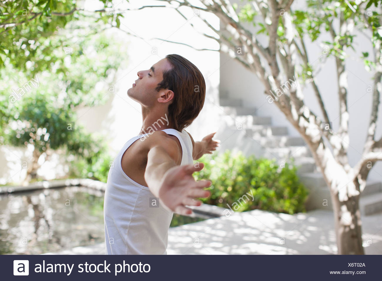 Man standing with arms outstretched - Stock Image