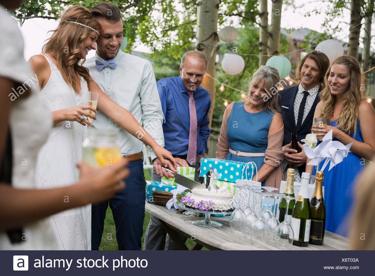 Bride and groom cutting cake backyard wedding reception - Stock Image