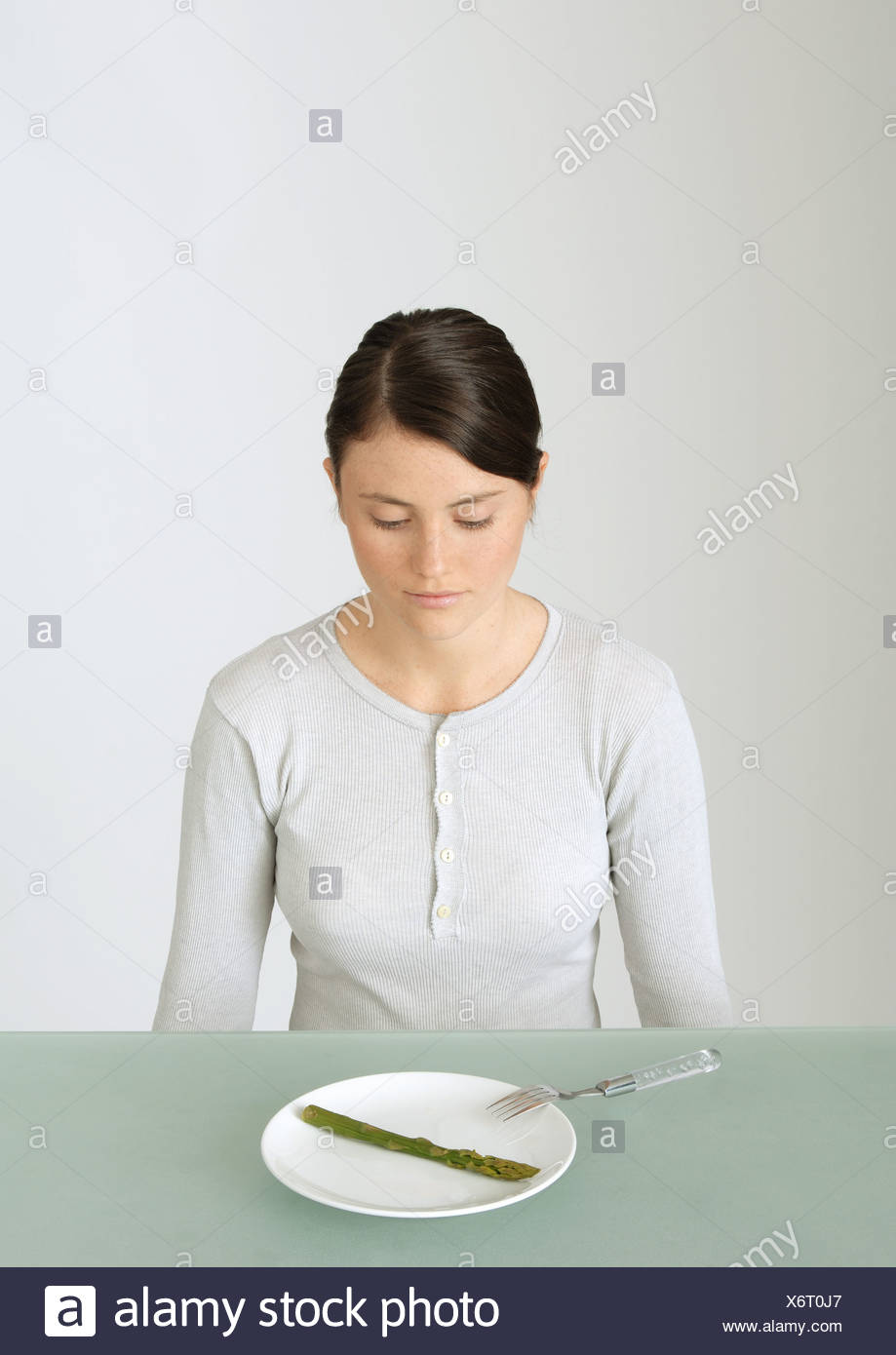 Young woman looking down at plate with single asparagus - Stock Image