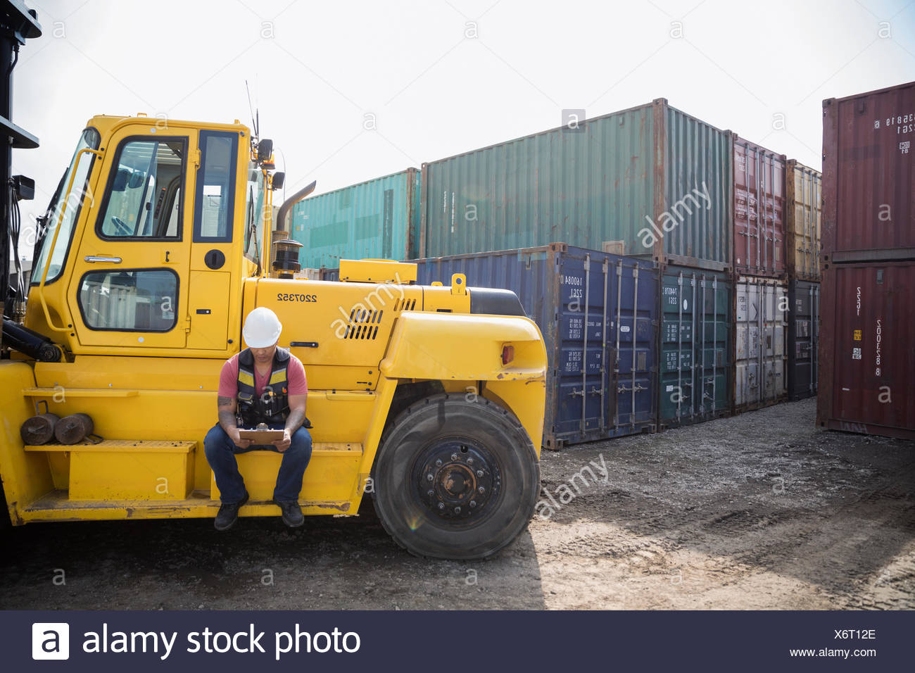 Male worker with clipboard sitting at forklift in sunny industrial container yard - Stock Image