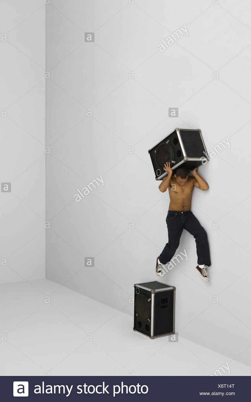 Man jumping off of perch atop speaker carrying second speaker on shoulders - Stock Image