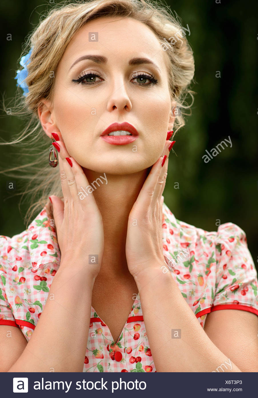 Portrait of a mid adult woman holding her hands to her face - Stock Image