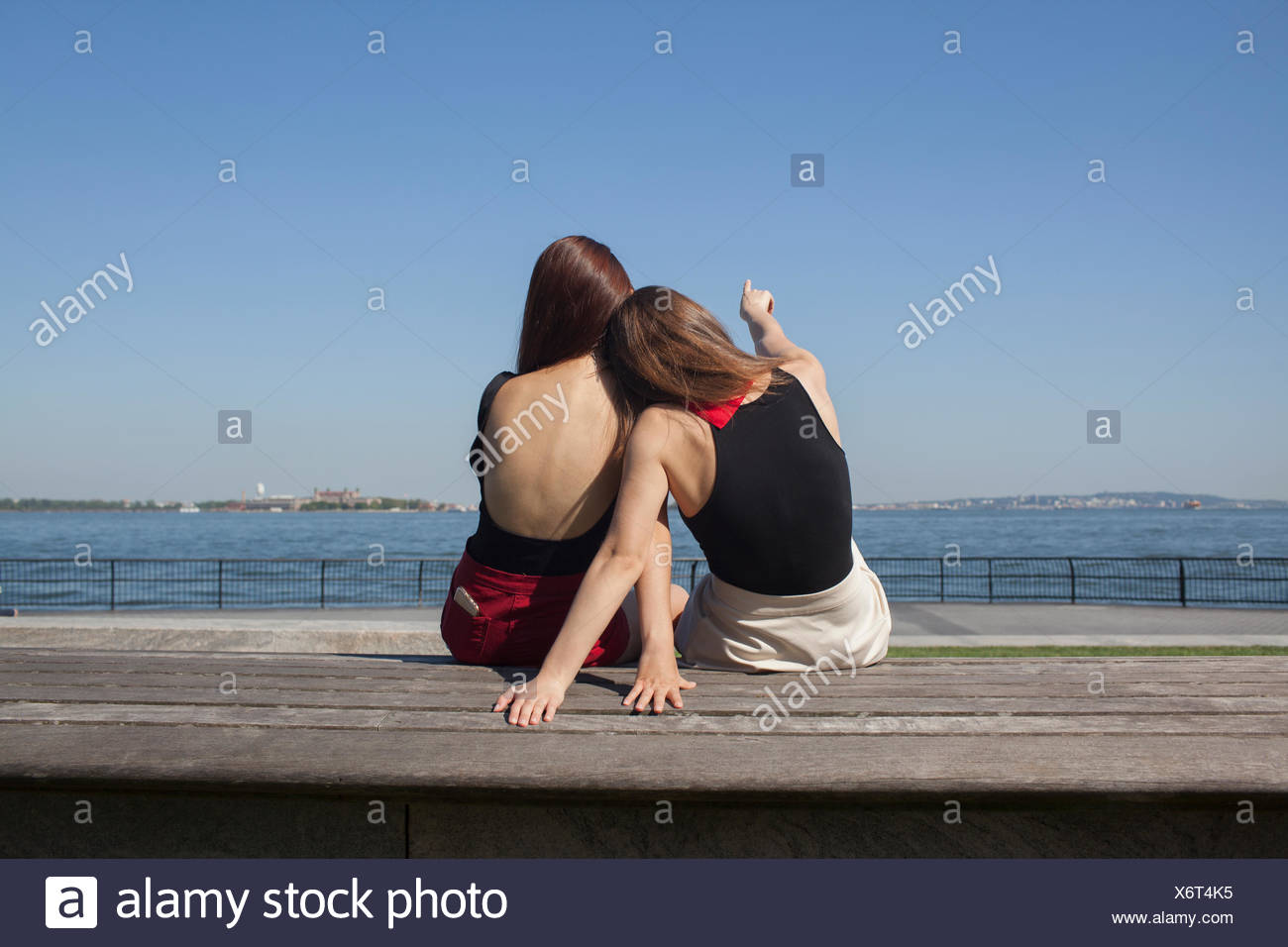 Back view of two young women sitting down - Stock Image