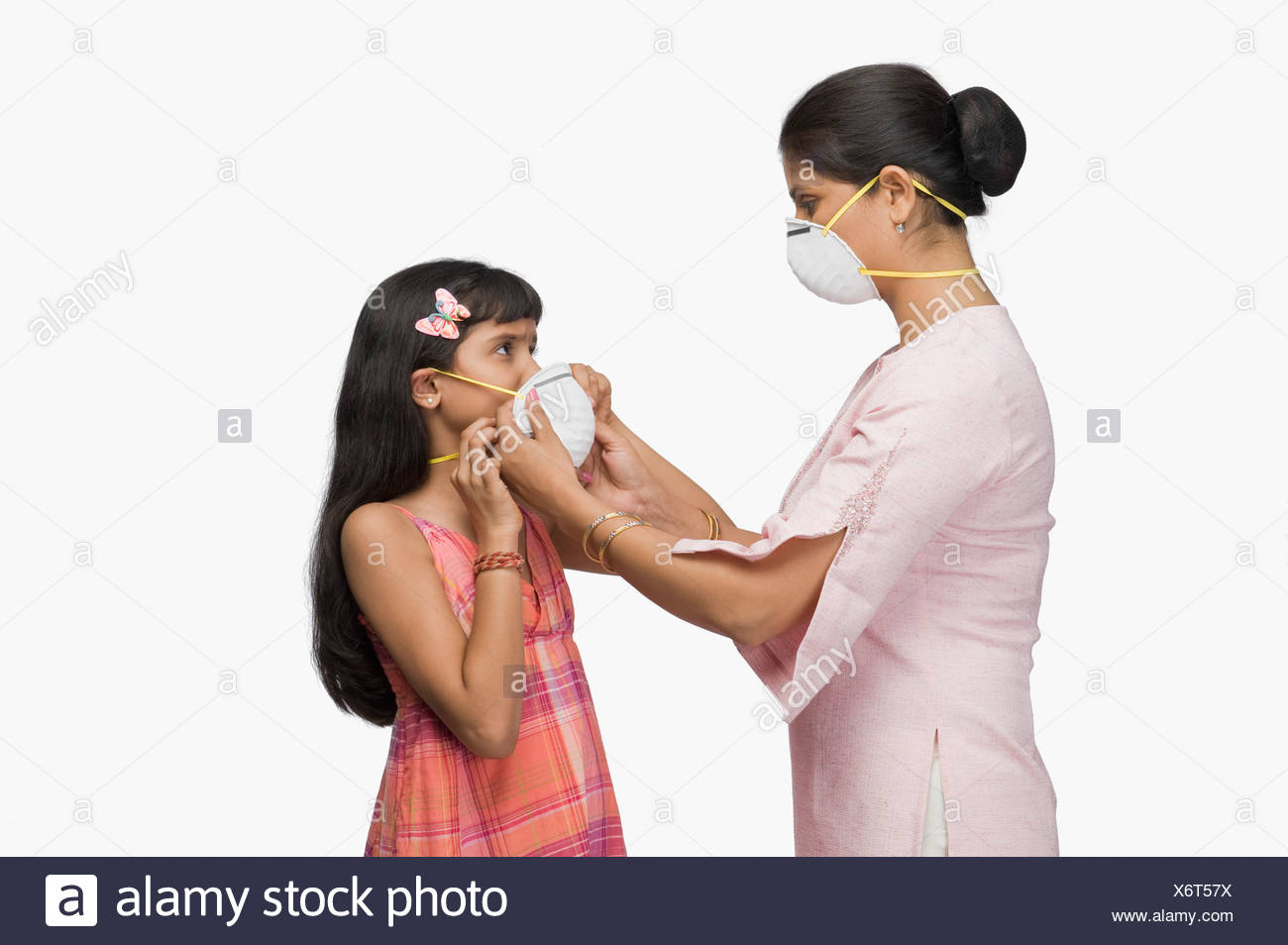 Young woman putting a pollution mask to her daughter - Stock Image