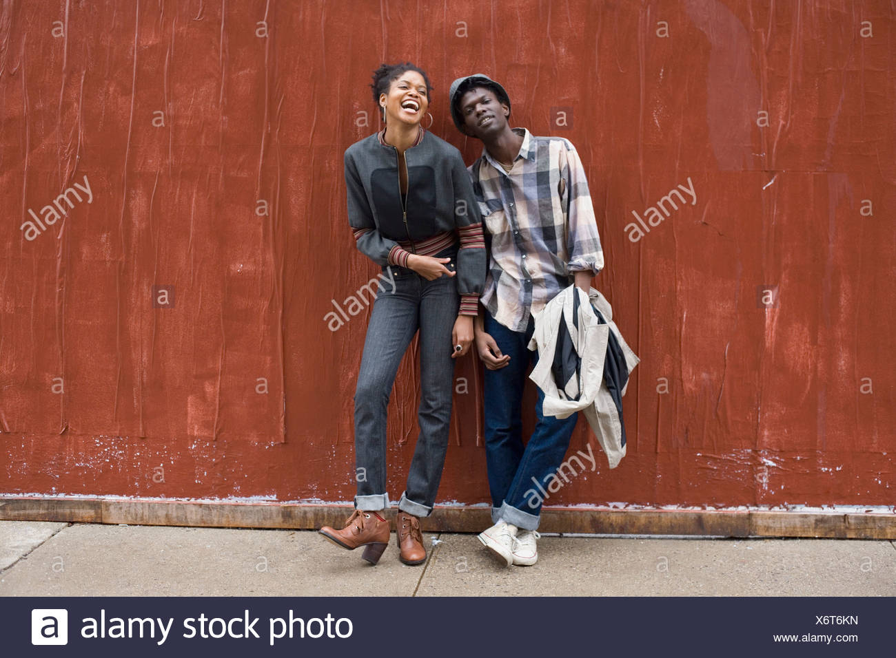 A young couple leaning against a wall Stock Photo