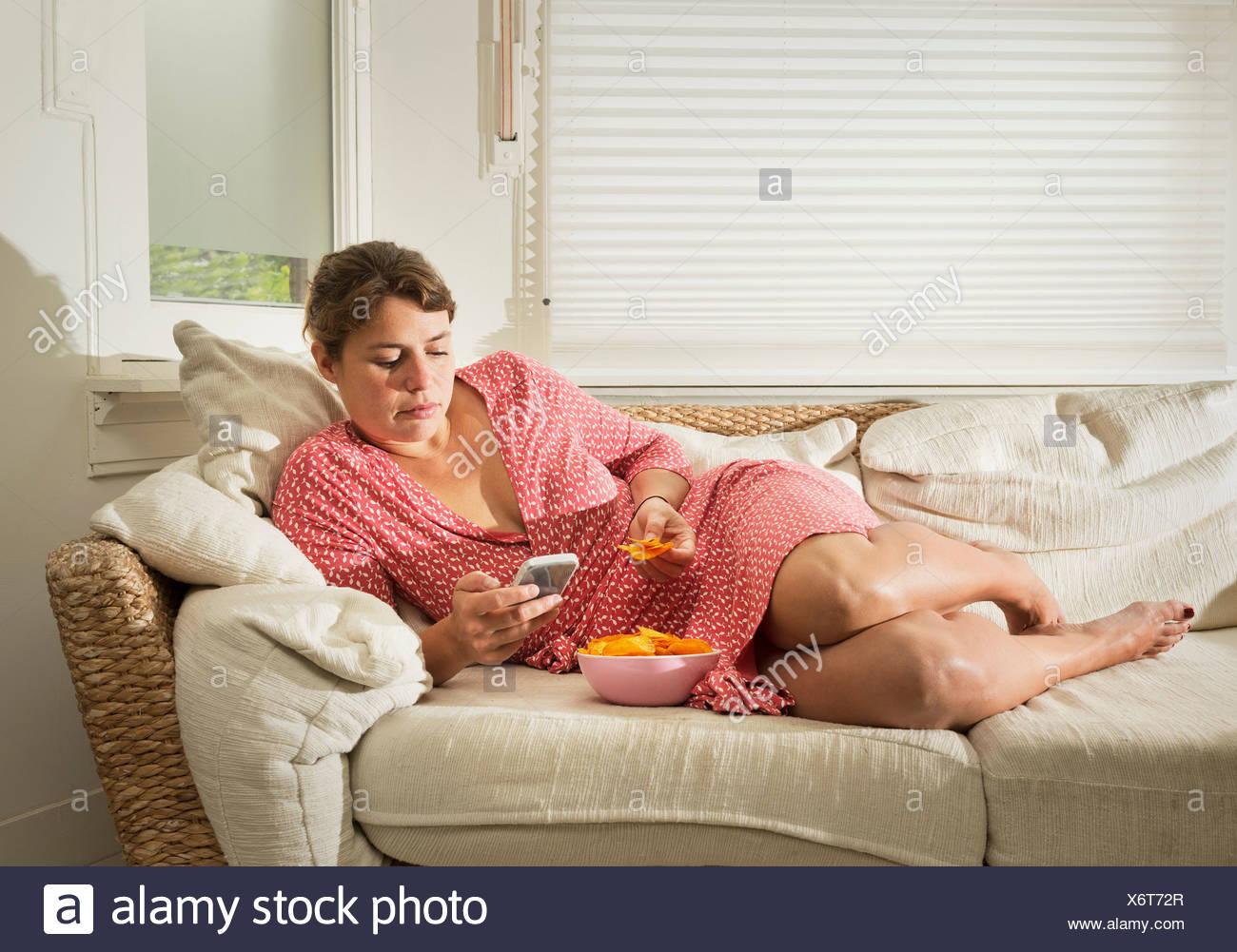 Woman lying on sofa eating bowl of crisps - Stock Image