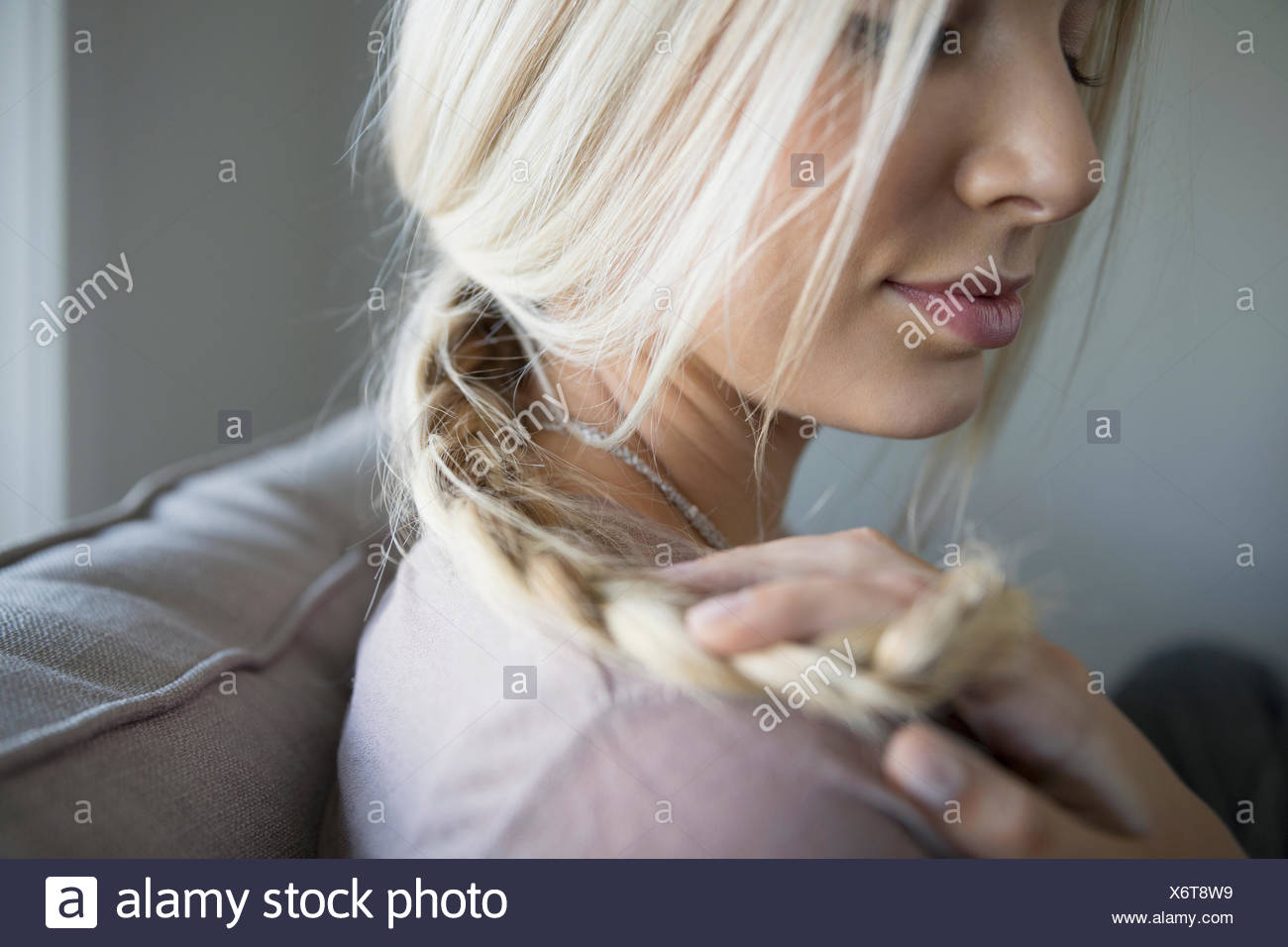 Close up blonde young woman holding braid - Stock Image