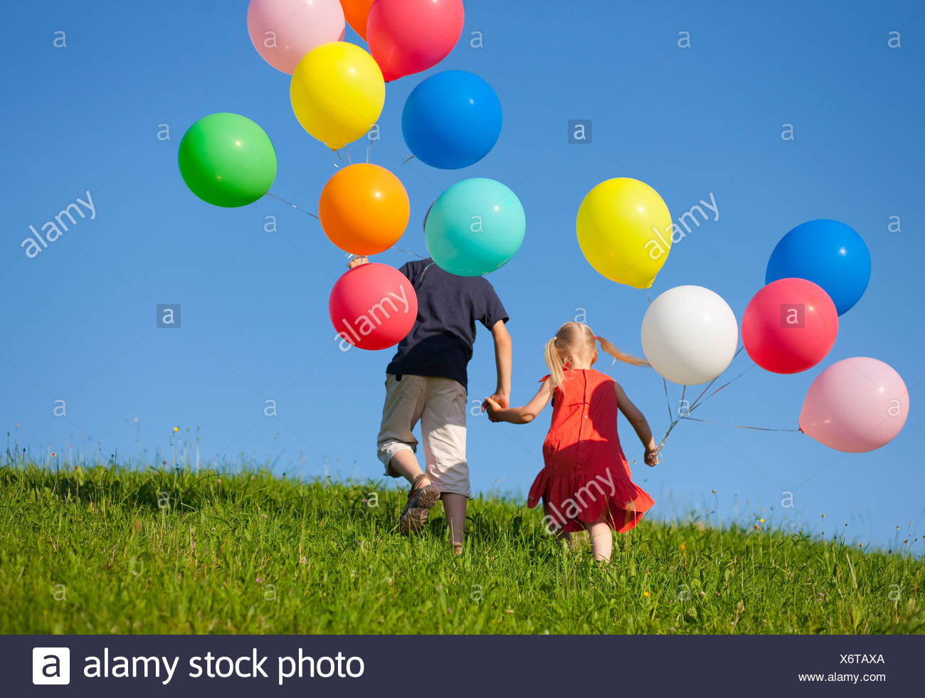 Children with colorful balloons in grass - Stock Image