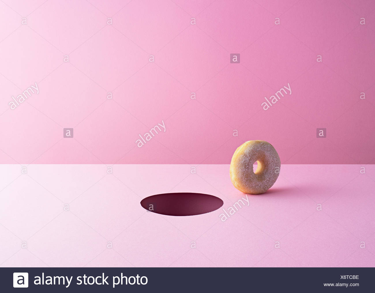 Doughnut and hole on pink ground - Stock Image