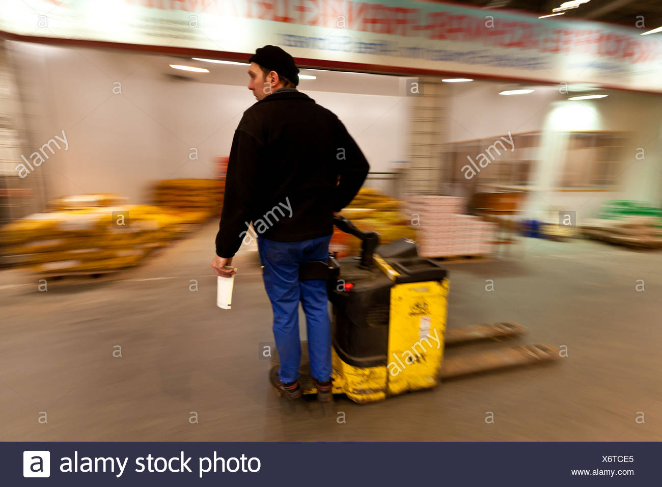 Workers drives hand lift with goods in a wholesale for fresh produce, fruits and vegetables, Frankfurt, Hesse, Germany, Europe - Stock Image