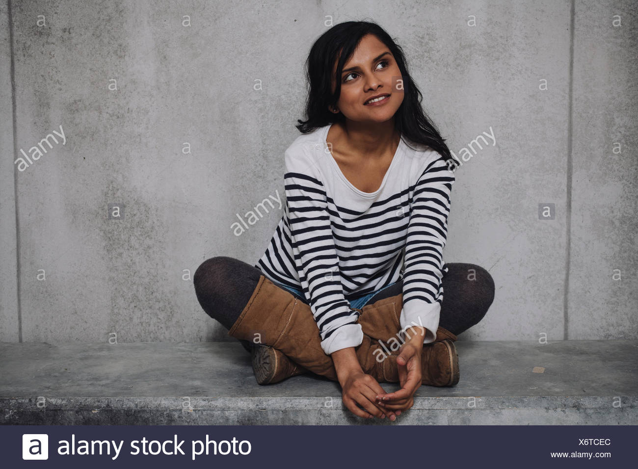 Female Indian sitting on concrete wall Stock Photo