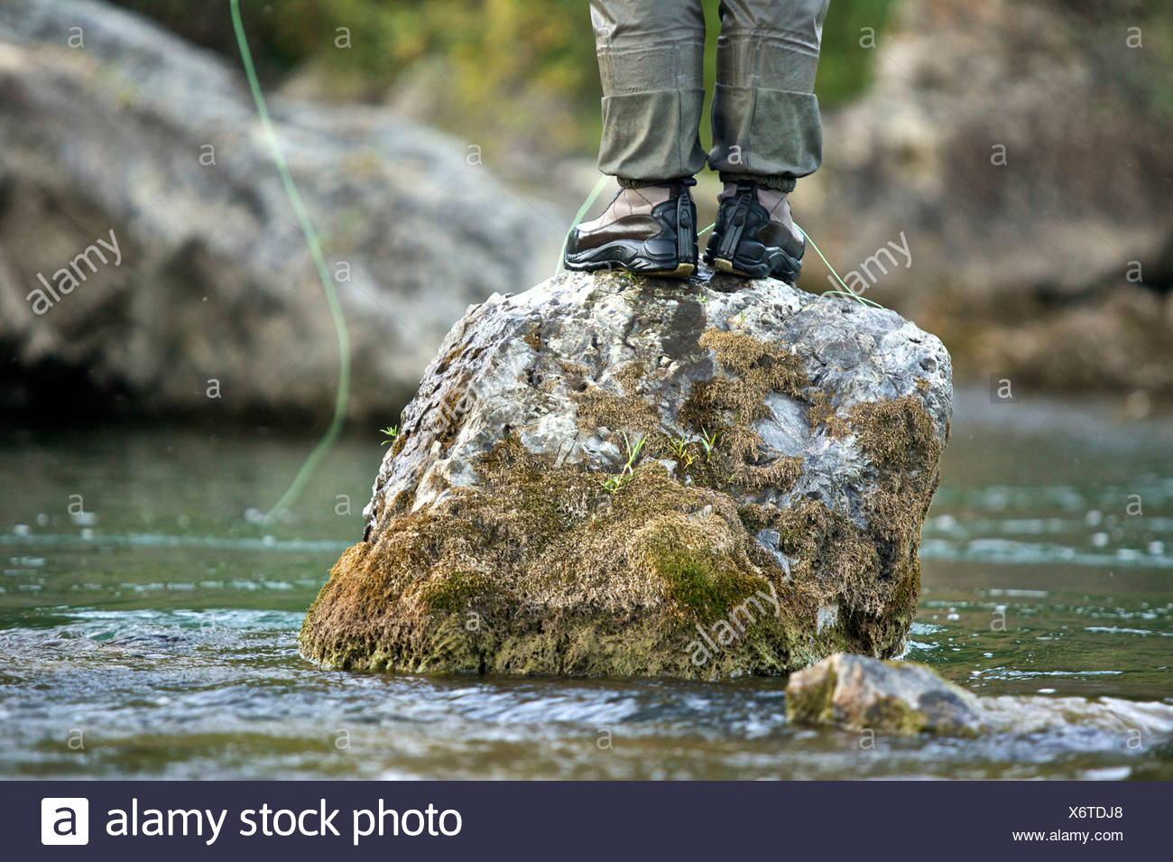 A man fishes from a rock on a river in Wyoming. - Stock Image