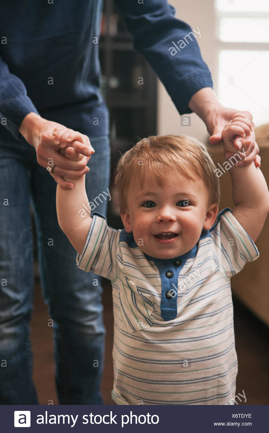 Little boy learning to walk with help from mother Stock Photo