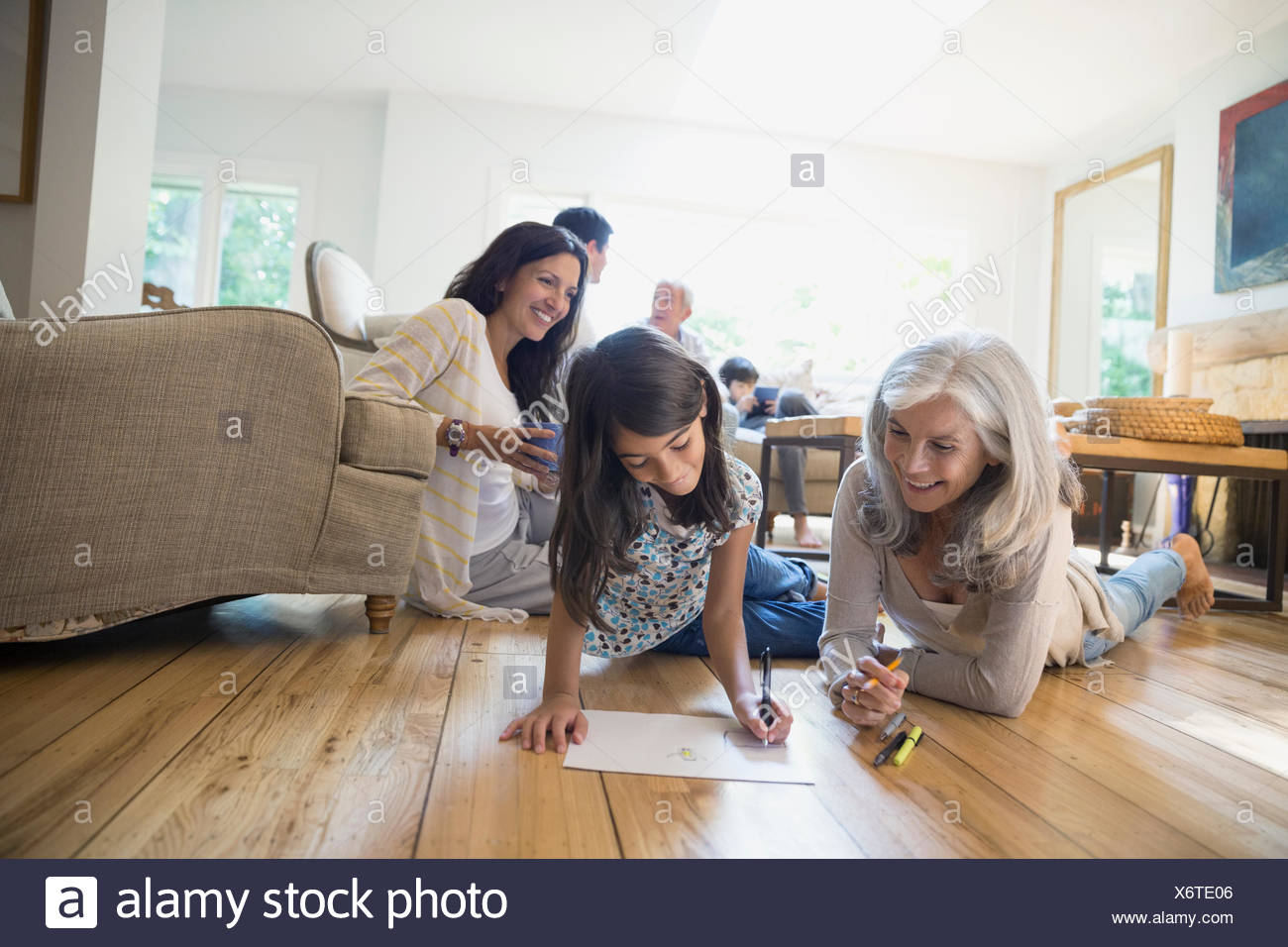 Grandmother and granddaughter coloring in living room - Stock Image