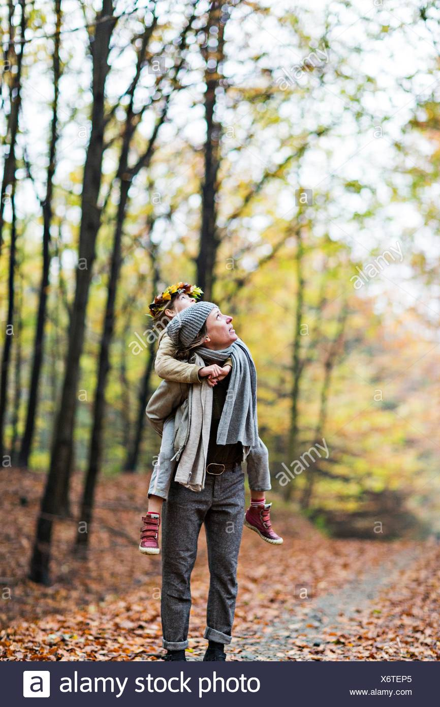 Mother giving daughter piggyback ride in autumn forest - Stock Image