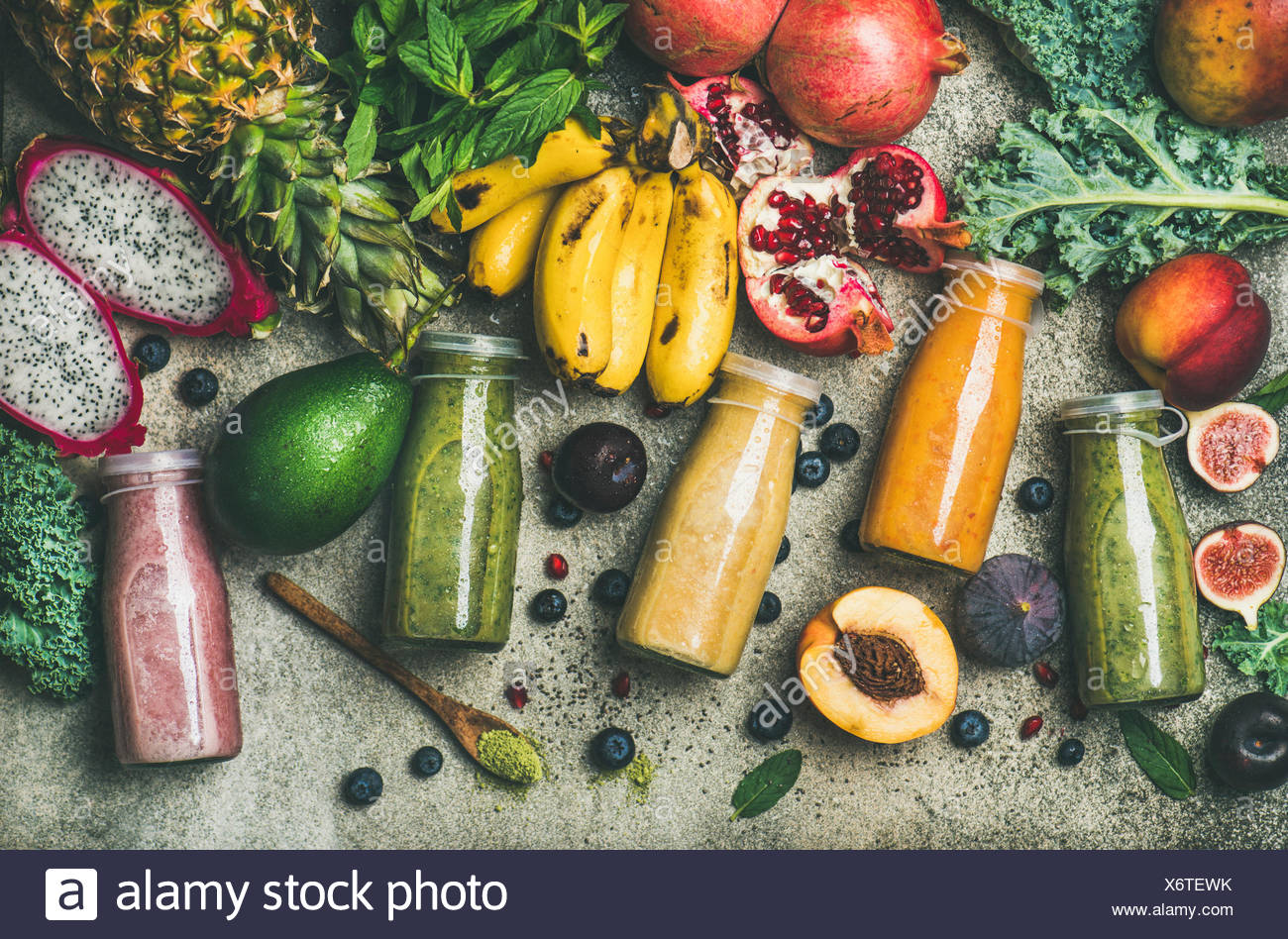 Flat-lay of colorful smoothies in bottles with fresh tropical fruit and superfoods on concrete background, top view. Healthy, clean eating, vegan, veg Stock Photo