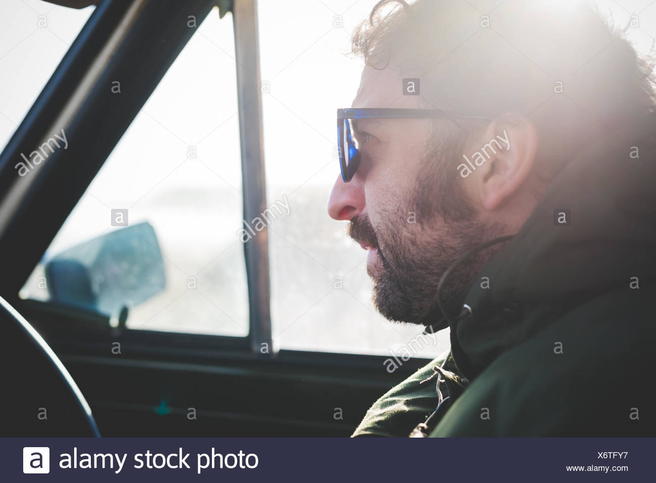 638b9c3b8044 Close up of mid adult man wearing sunglasses in sunlit car - Stock Image