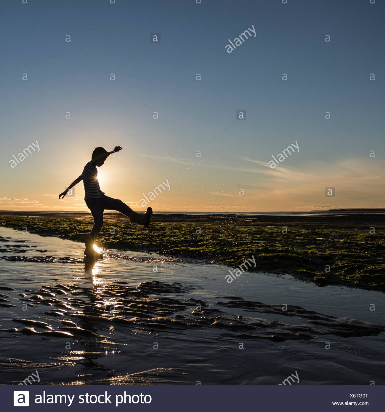 Silhouette of a boy kicking water at the beach - Stock Image