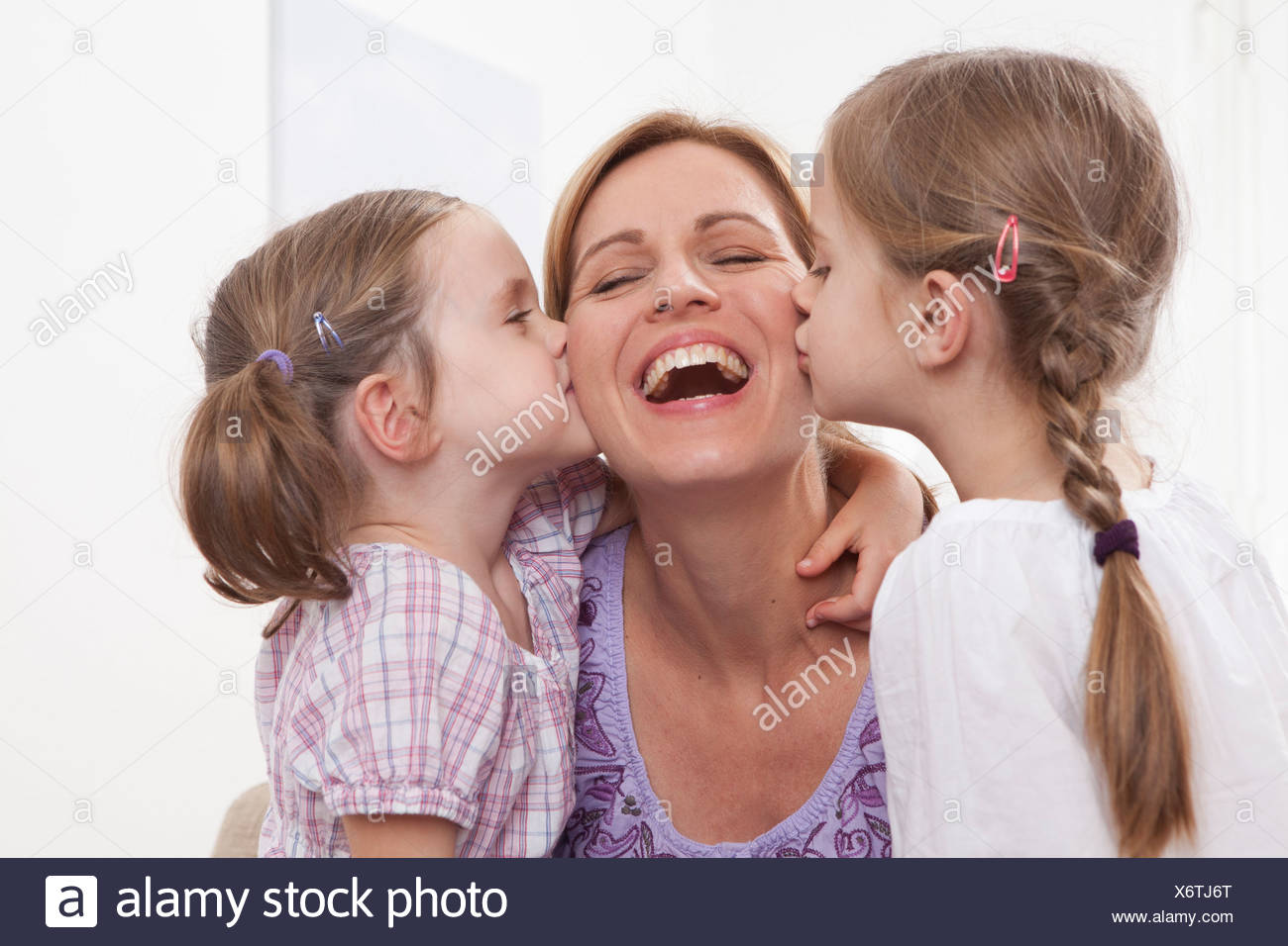 Germany, Munich, Girls (4-7) kissing on mother's cheek Stock Photo