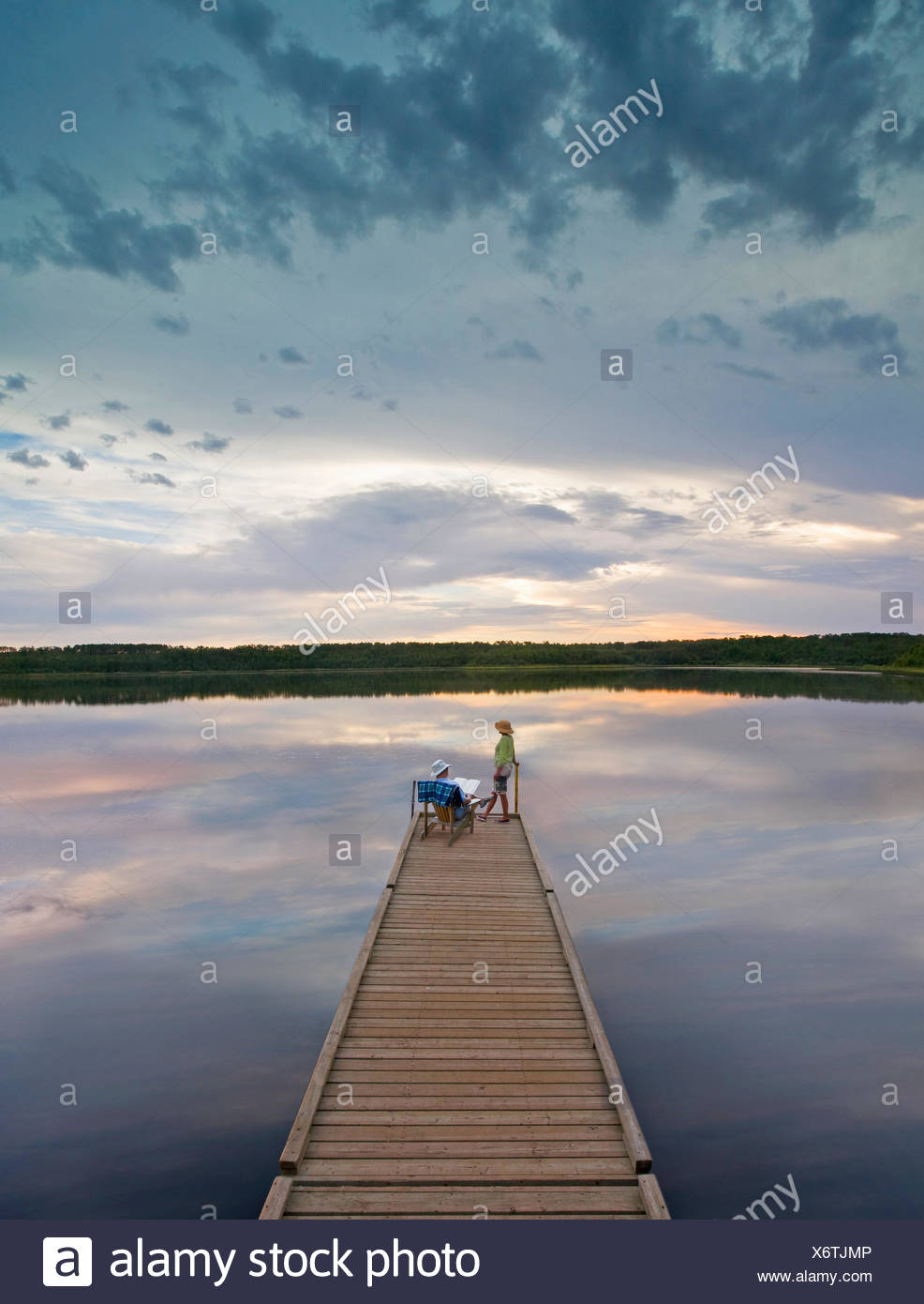 A couple, man and woman sitting at the end of a long wooden dock reaching out into a calm lake, at sunset. - Stock Image