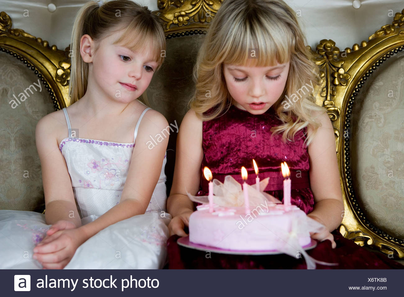Little girl and friend holding a birthday cake with lit candles Stock Photo