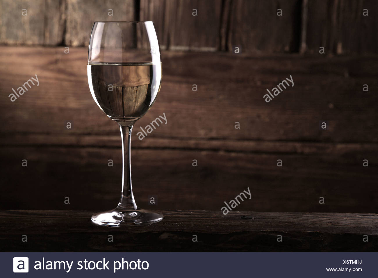 A glass of white wine in front of a rustic wooden wall - Stock Image