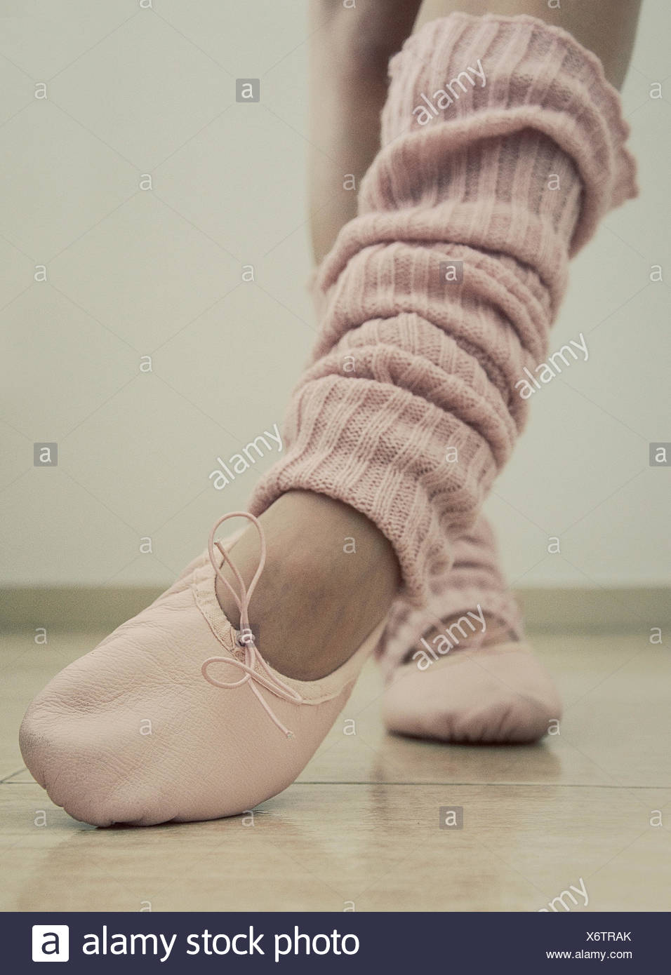 Close-up of a teenage girl's legs, ballet shoes and leg warmers - Stock Image