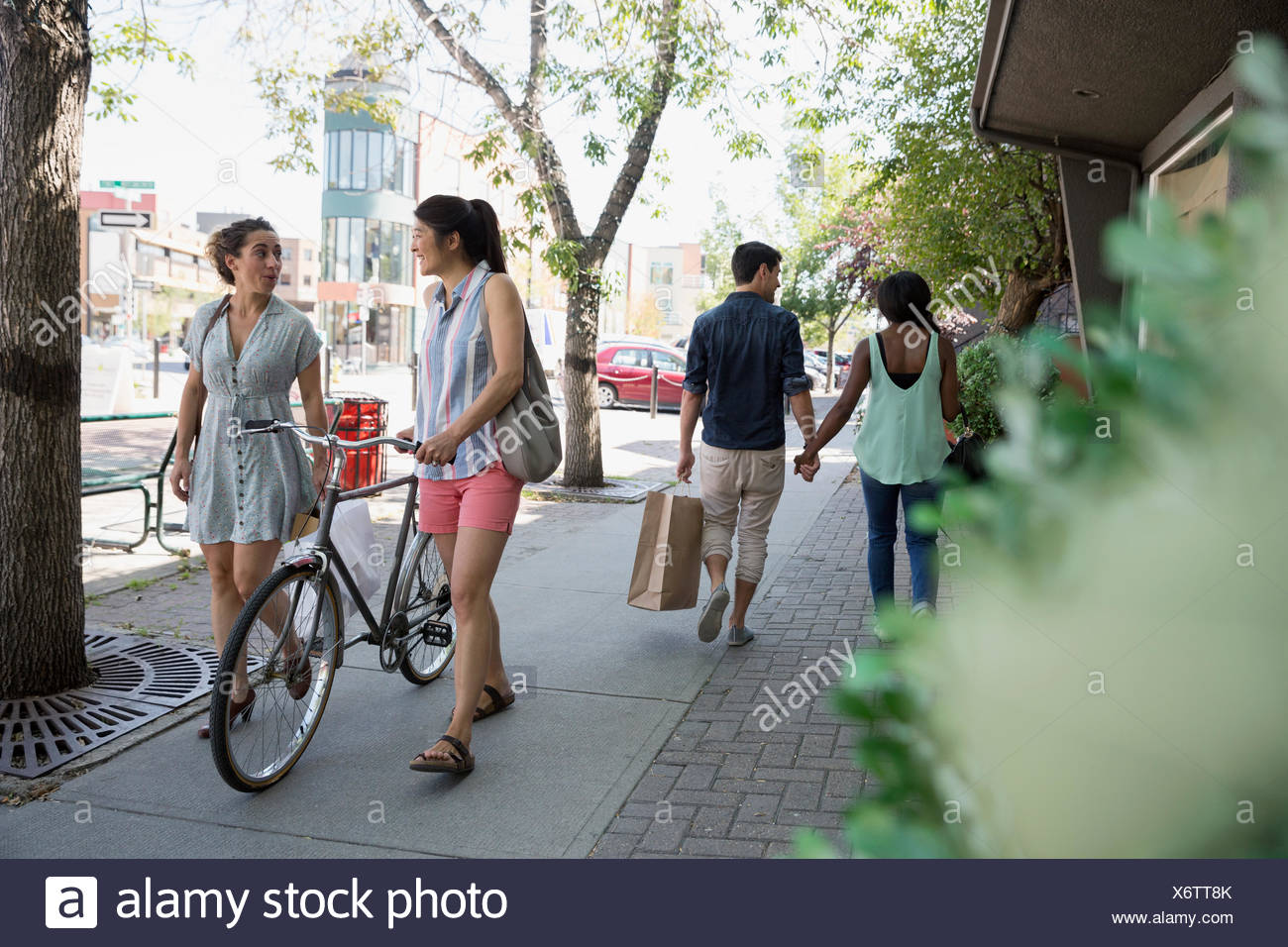 People walking with bicycle and shopping bags on urban sidewalk - Stock Image