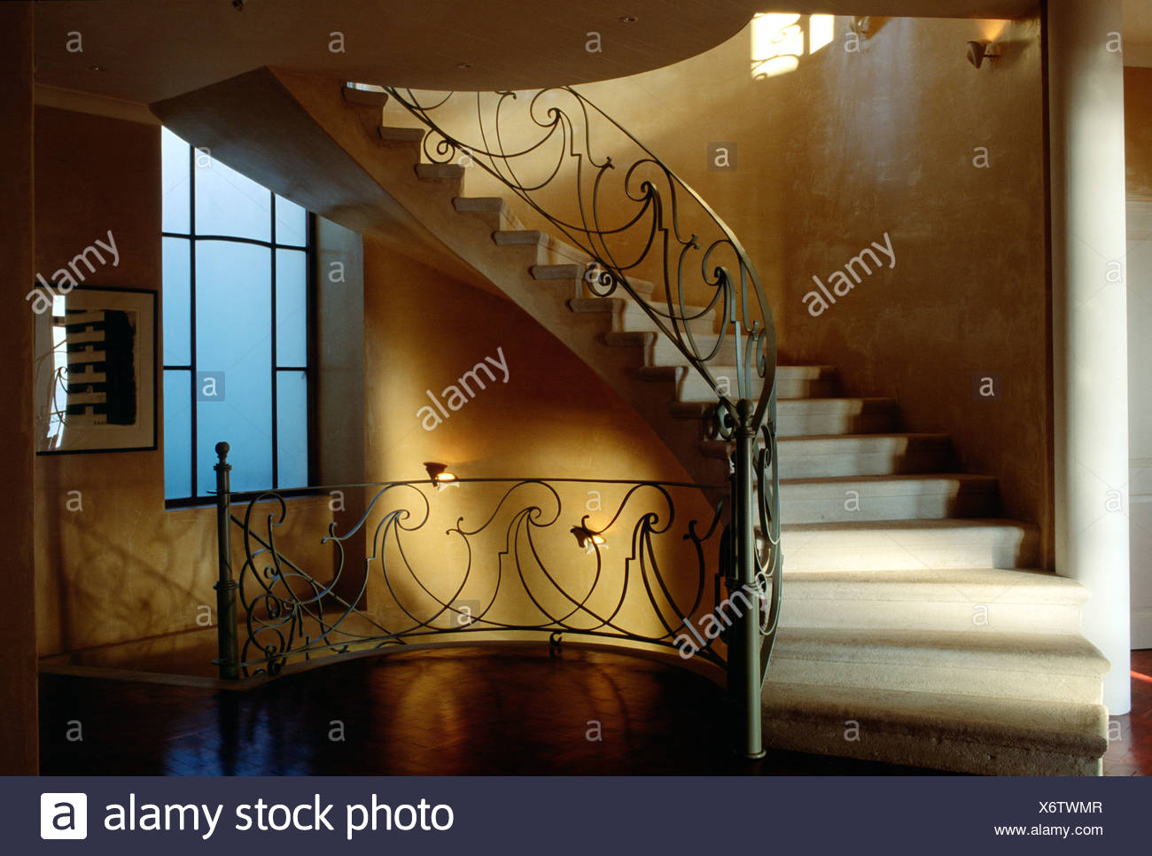Curved Staircase Wrought Iron Railing, Dark Yellow Walls, Landing Between  Two Floors Tall Window