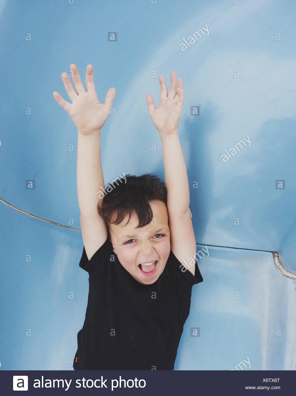 Boy standing with his arms in air - Stock Image