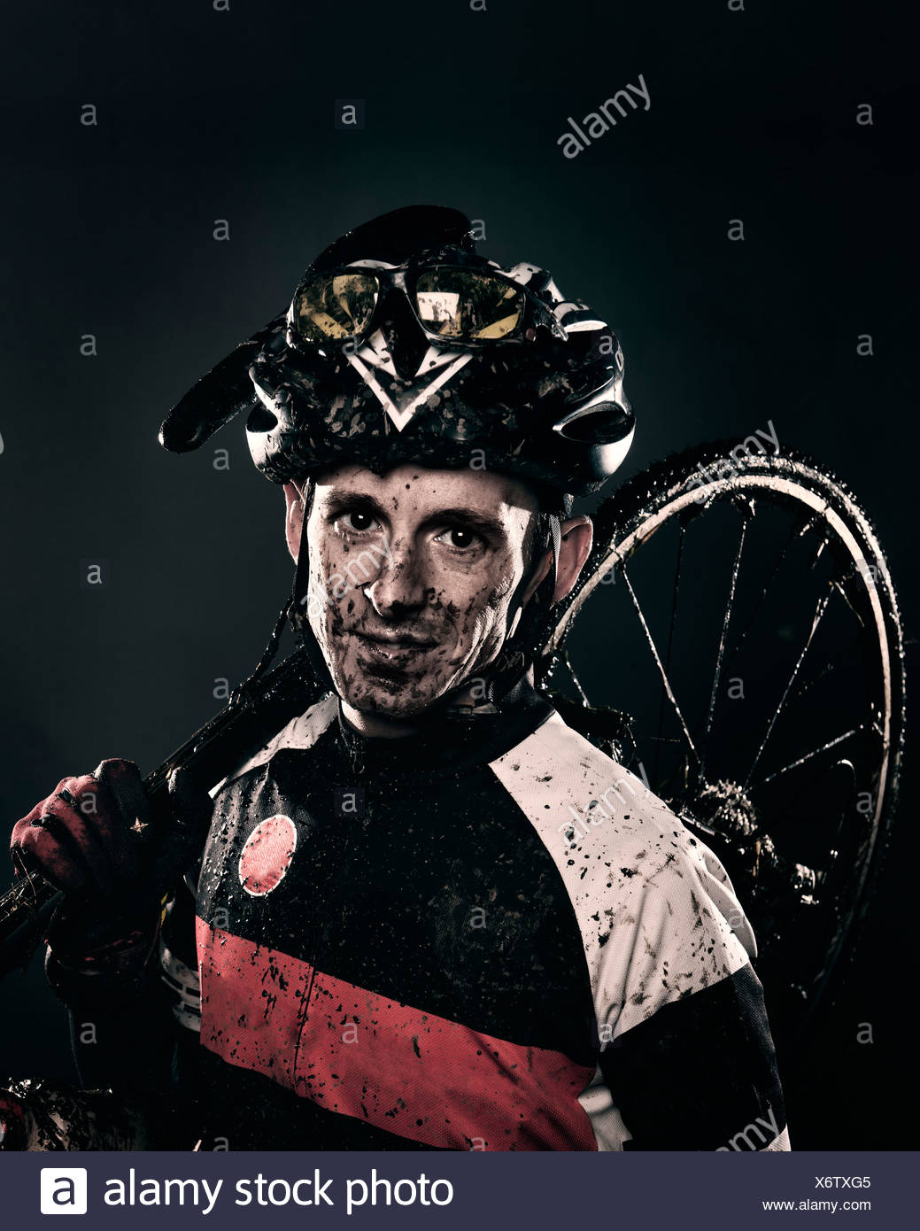 Mud splattered cyclist carrying bicycle - Stock Image
