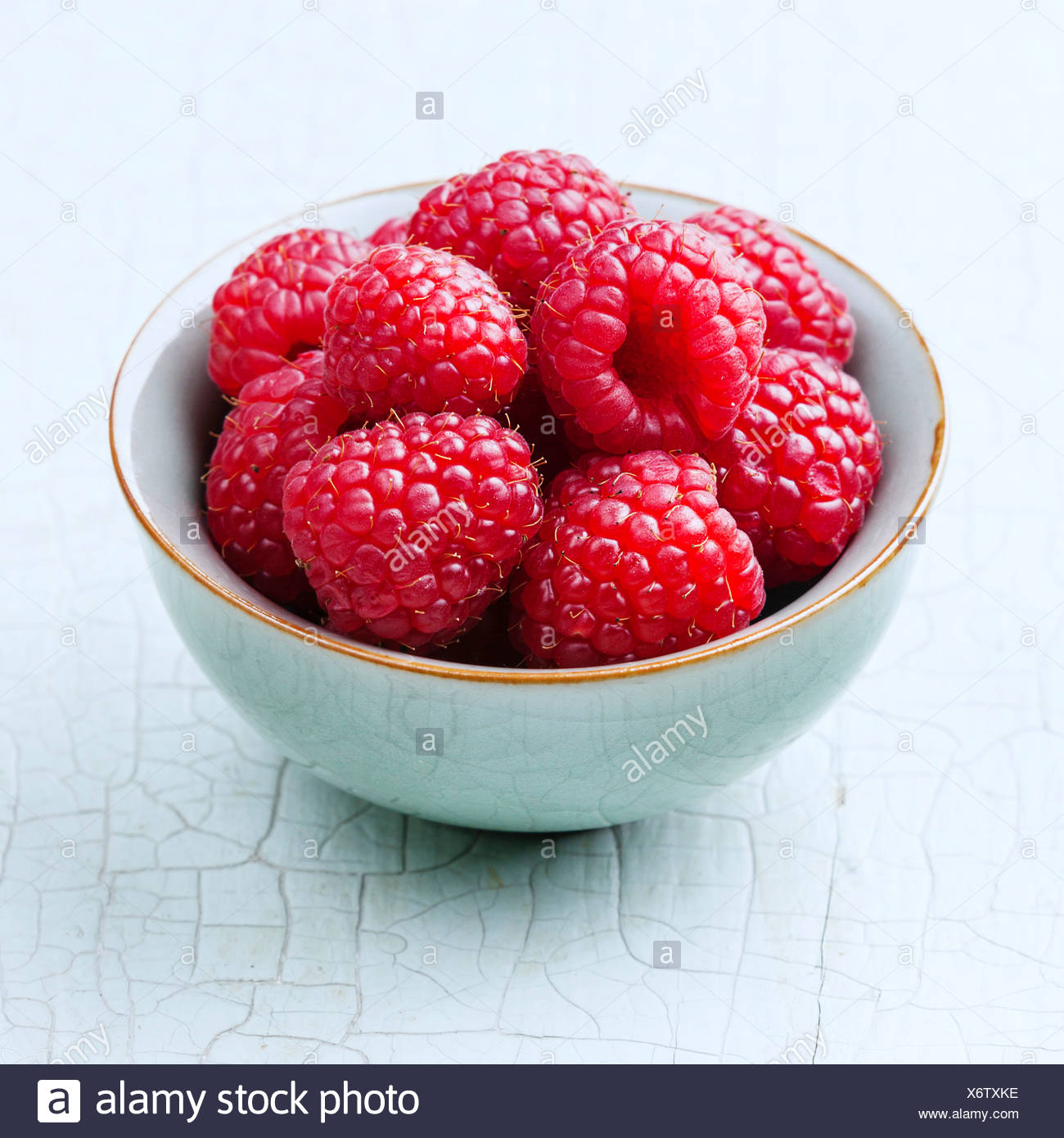 Raspberries in bowl on blue background - Stock Image