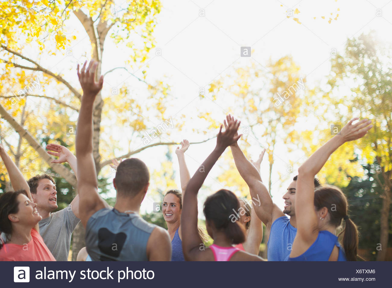 Fitness class giving each other a high five after class. - Stock Image