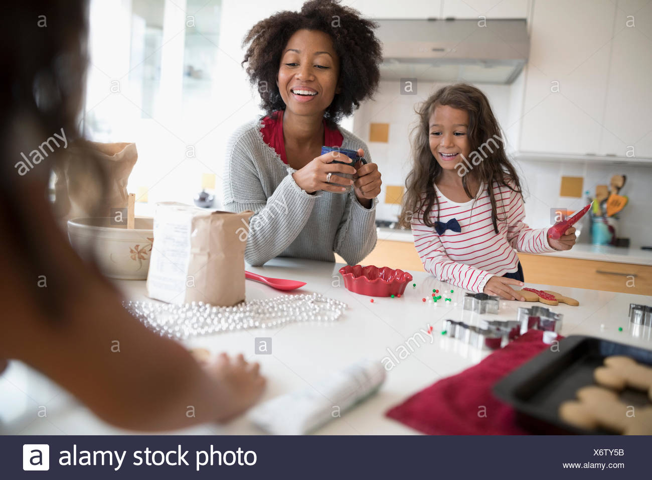 Mother and daughters decorating Christmas gingerbread cookies in kitchen - Stock Image