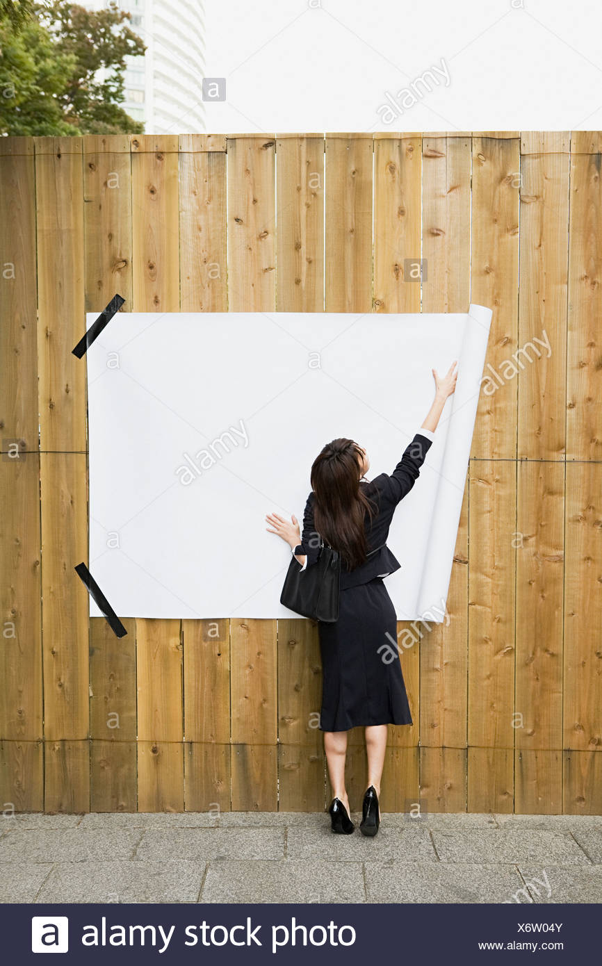 A businesswoman attaching paper to a fence - Stock Image