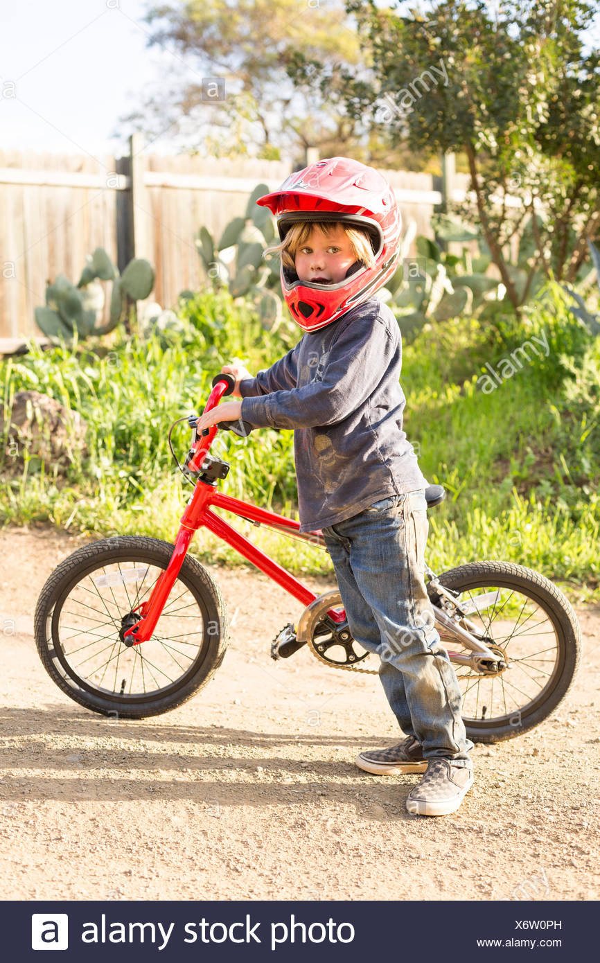Boy with a bicycle, wearing helmet - Stock Image