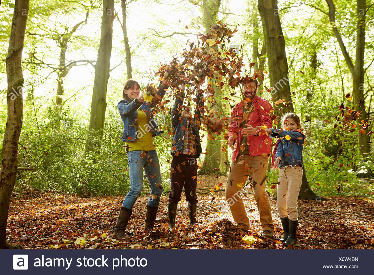 A family throwing dried leaves into the air in the woods in autumn. - Stock Image