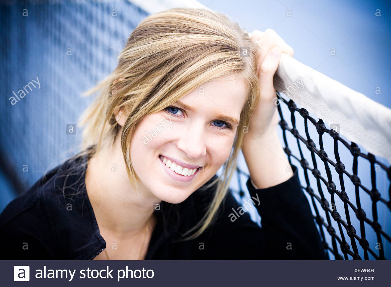 A teenager leans against a tennis court net in Charlotte, North Carolina. - Stock Image