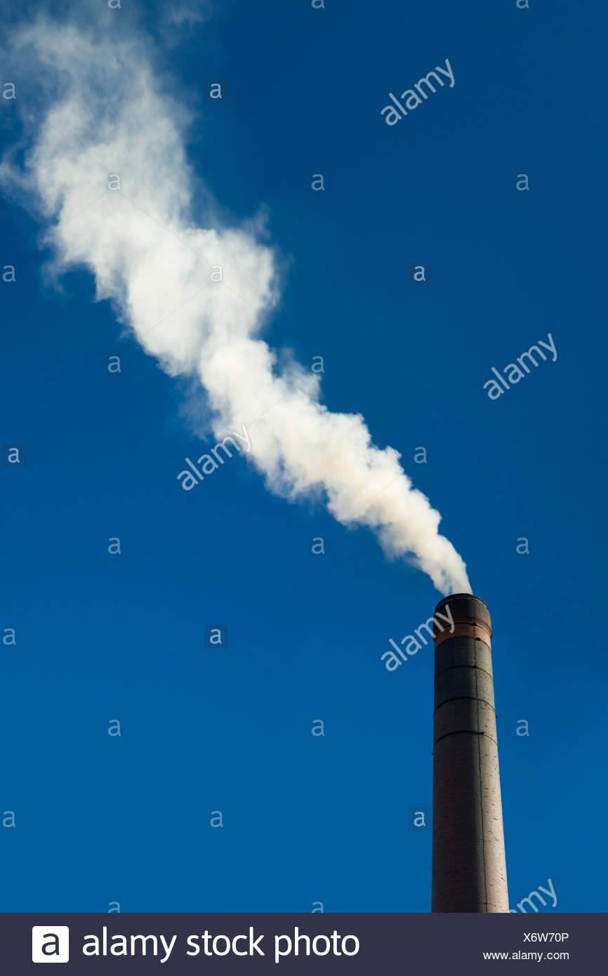 Smoke coming from a chimney - Stock Image