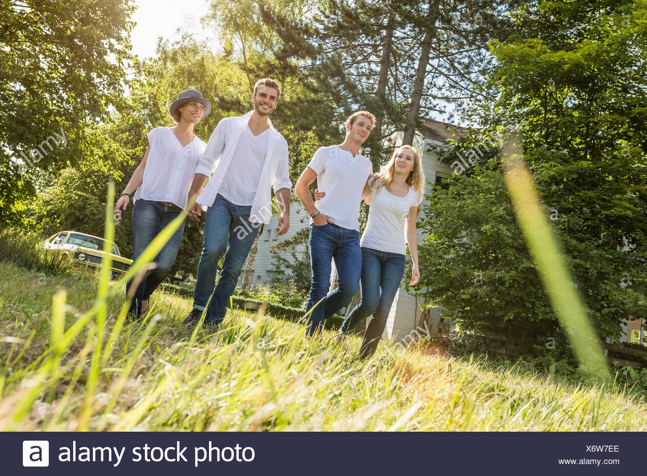 Group of people walking through forest - Stock Image