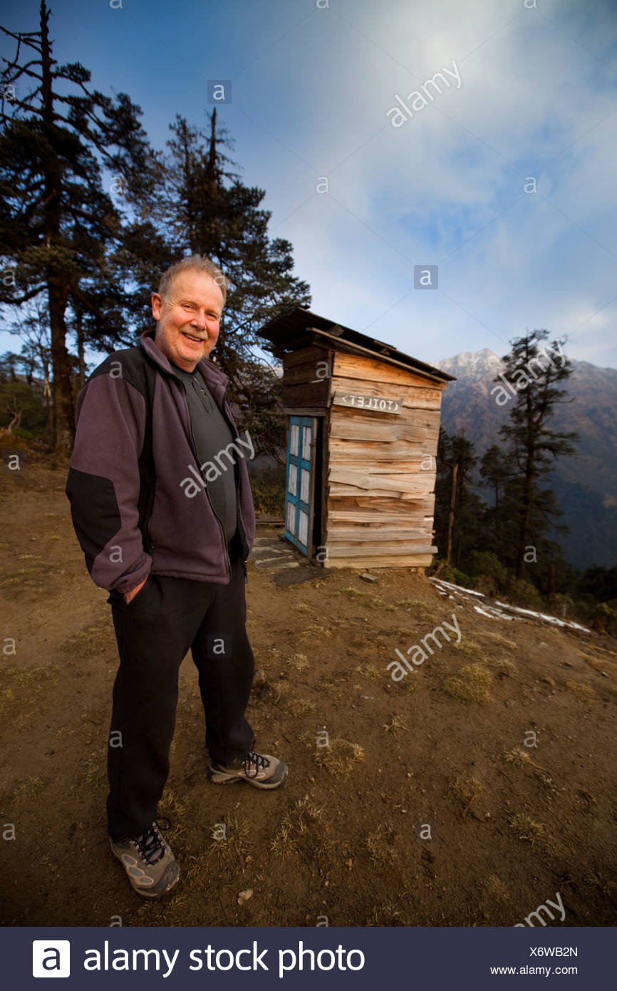 A male trekker standing inf ront of a wooden outhouse in the high alpine of Nepal. - Stock Image