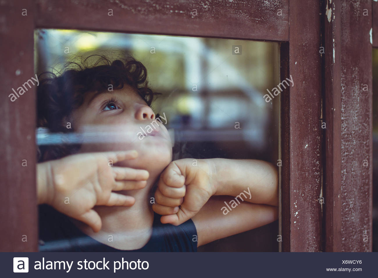 Boy looking out of a window - Stock Image