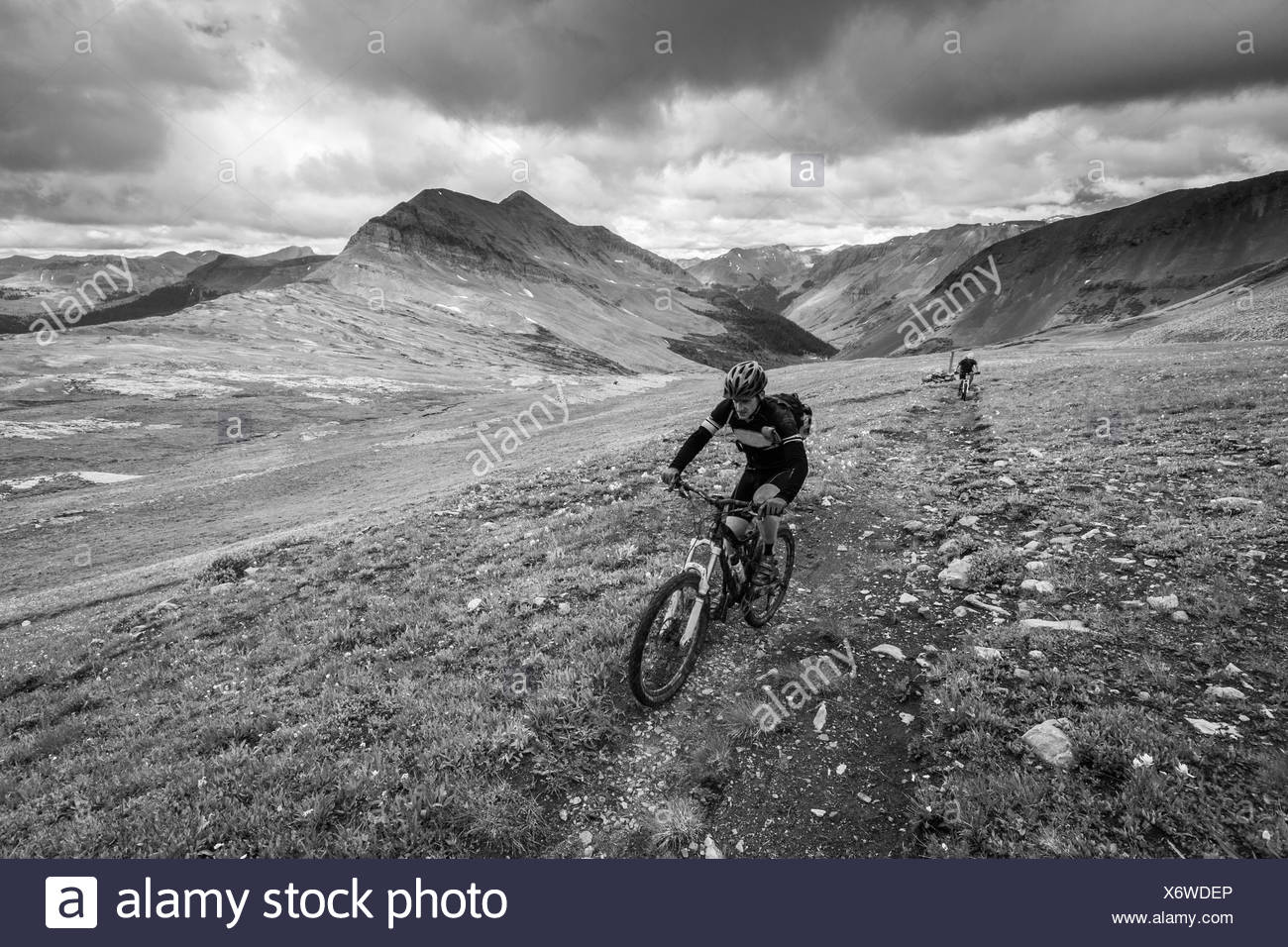 Two men riding on a trail in the mountains. Black and white. - Stock Image