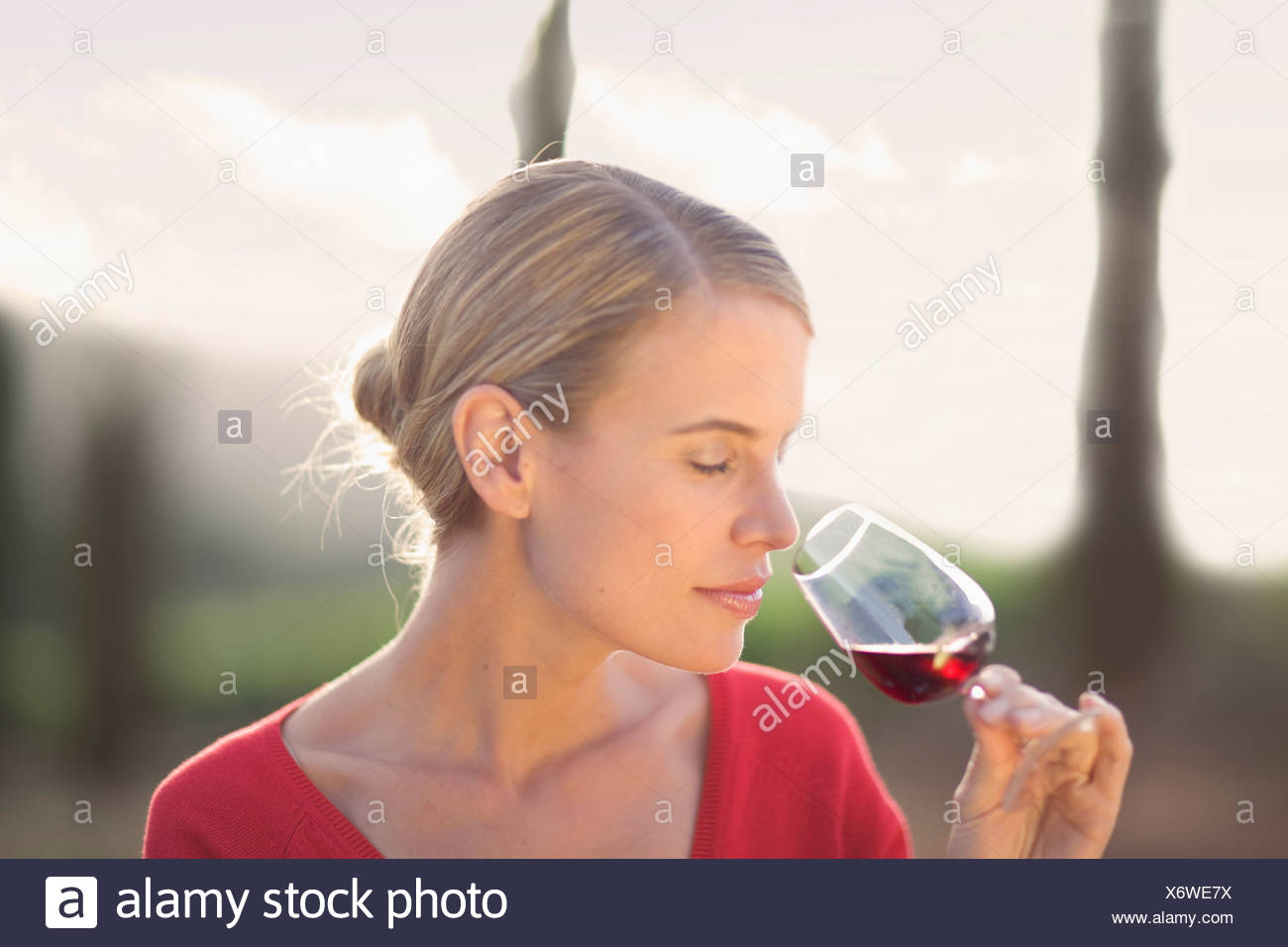 Woman enjoying a glass of red wine - Stock Image