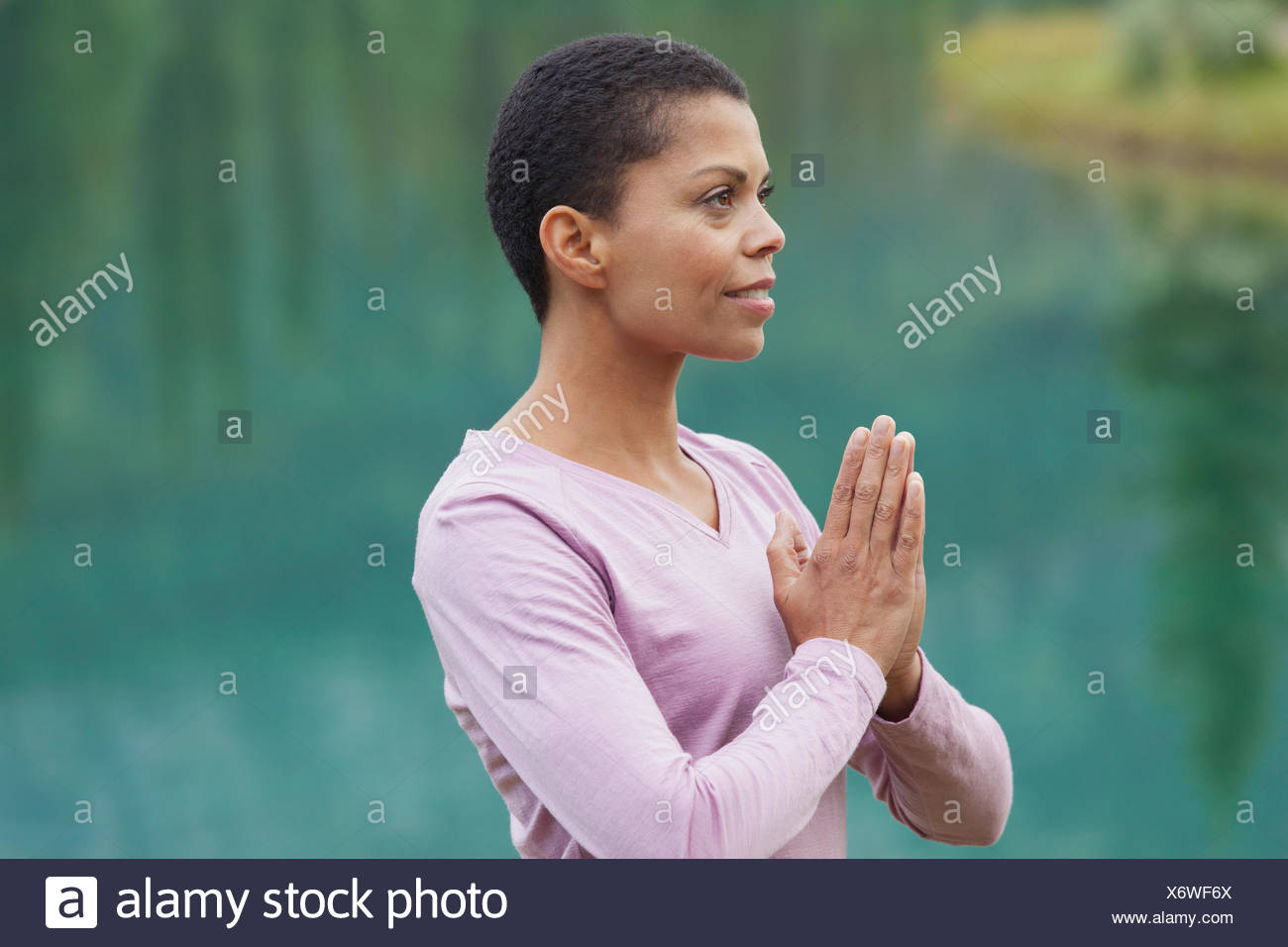 portrait of african american woman in yoga pose outdoors - Stock Image